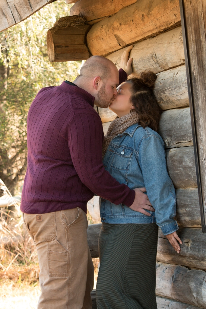 couple embraced outside against log cabin kissing fall colors