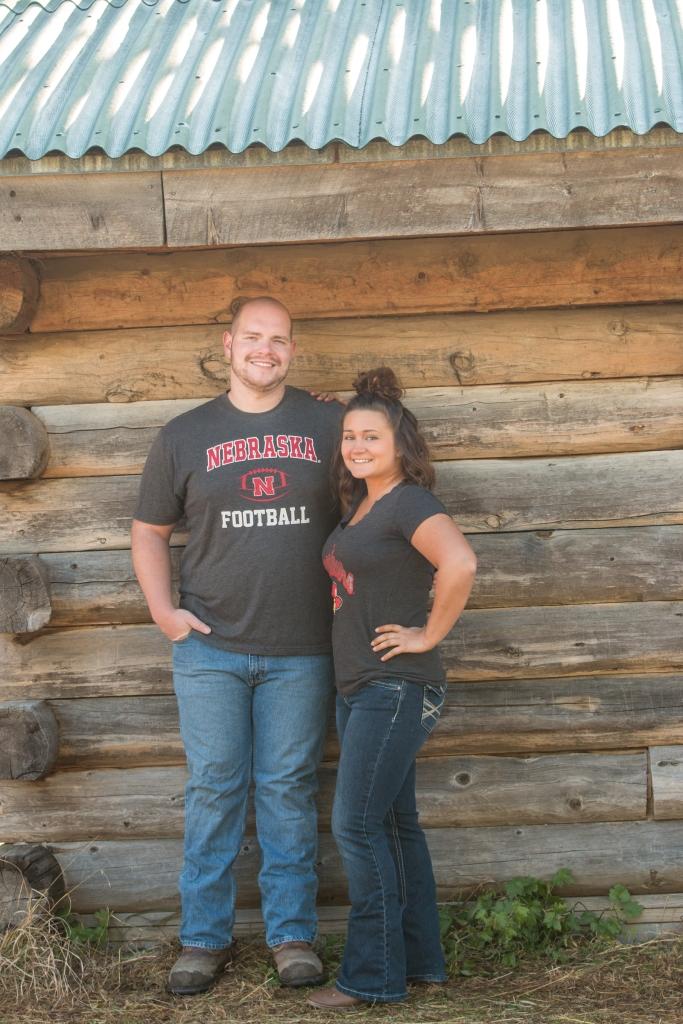 full length of couple against log cabin in Nebraska Husker jerseys