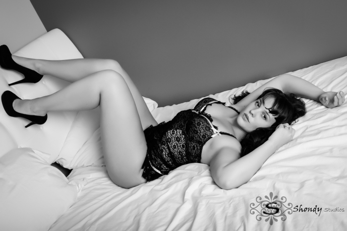 black and white of woman laying on bed legs against headboard in lingerie