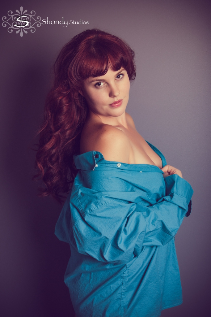 woman exposing shoulder in teal button up shirt red hair