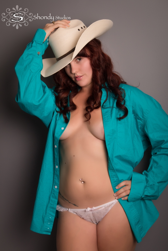 woman standing against gray wall with cowboy hat and open teal shirt